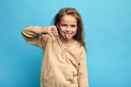 Photo pour funny crazy girl gesturing thumbs down and sticking out her tongue isolated over blue background. close up portrait, isolated blue background, child making faces, kid having fyn, teasing somebody - image libre de droit