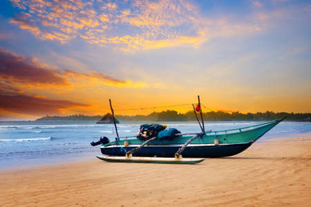 Photo pour Beautiful seascape. Against the background of the sunset sky and the ocean, an old fishing boat. Sri Lanka - image libre de droit