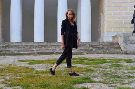 Foto de A pretty teenage girl n a business black suit is stands - Imagen libre de derechos