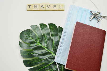 Photo pour Passport with medical mask and keychain in the form of aircraft on a green palm leaf on white background. Travel word made from wooden cubes. Travel during quarantine - image libre de droit