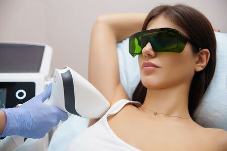 Photo pour Laser epilation and cosmetology in beauty salon. Hair removal procedure. Laser epilation, cosmetology, spa, and hair removal concept. Beautiful brunette woman getting hair removing on underarm - image libre de droit