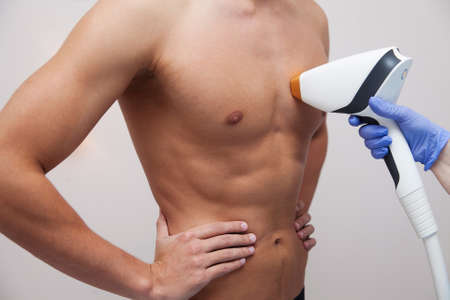 Photo pour Muscular athlete man with smooth clear skin. Epilation and depilation of hair in beauty salon. Male laser hair removal concept. Beautician using modern apparatus for procedures. Skin and Beauty Care - image libre de droit