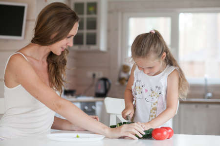 Photo for Happy family mother and child posing at home. Beautiful young mom and little daughter having fun and preparing vegetables for salad in a white kitchen in a Scandinavian style interior. Healthy food - Royalty Free Image