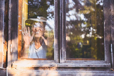 Photo pour Happy smiling emotional elderly woman having fun posing by open window in rustic old wooden village house in straw hat. Retired old age people concept. Quarantine in the country house - image libre de droit
