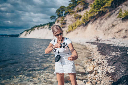 Photo for Elderly senior traveling backpacker mature woman tourist walking taking photos on coast background of sea, stones, rocks, blue sky. Retired people summer holiday vacation, active lifestyle concept - Royalty Free Image