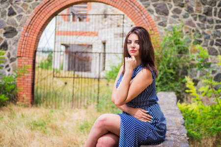 The brunette girl in a blue long dress against the background of a fence