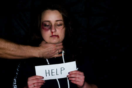 Photo pour A battered young wife with a bruised lip and nose, suffers from violence, beatings and bullying of her husband. A husband holds his battered and frightened wife by the throat. - image libre de droit