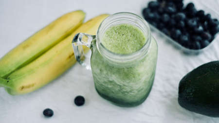 green avocado banana blueberries smoothie in a glass jar over white background, healthy eating,detox, summer diet