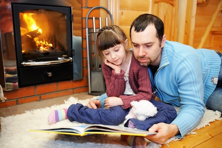 Photo pour Father and daughter reading a book in front of fireplace - image libre de droit