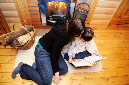 Mother and daughter reading a book in front of fireplace, top view