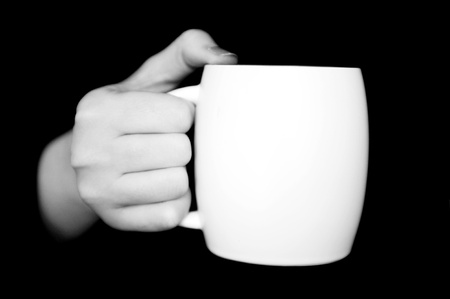 Hand holding white cup isolated on black background