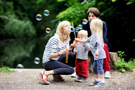 Happy family with two children having fun while blowing bubbles together in the park
