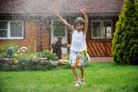 Little girl refreshing herself under splashes of water in a garden, slight motion blur