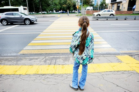 Photo for Adorableschool aged kid girl in glasses and fashion  clothes standing  near the pedestrian crossing on the city street - Royalty Free Image