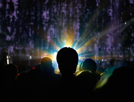 Silhouette of man standing in a crowd with halo around the head in front of stage with abstract background