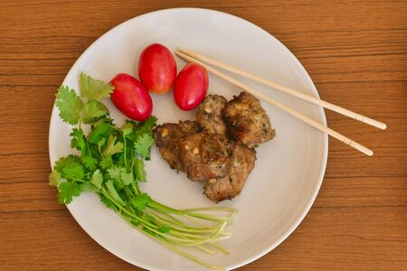 Tasty roasted pork with fresh vegetable and chopsticks in white plate on wood table