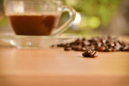 scattered roasted coffee beans on wooden table and a cup of coffee background