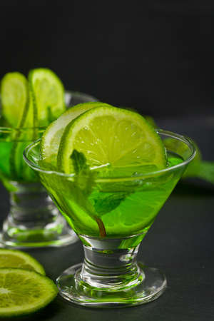 A shot of Green Vodka with Lime and Mint. Selective focus