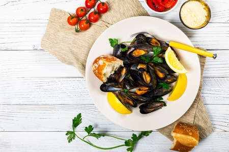 Photo pour Delicious Seafood Mussels with Lemon and Parsley. Clams in the Shells on Wooden Background. Selective focus. - image libre de droit