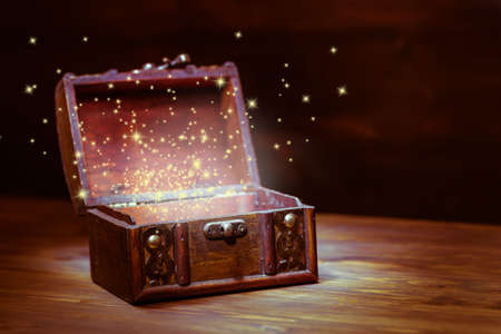 beautiful background of mystery chest with light miracle on wooden background with place for text, closeup