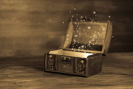 Photo pour beautiful retro chest with sparkles on wooden background with place for text, closeup, sepia style - image libre de droit