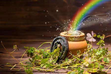 St Patricks day decoration with magic light rainbow pot full gold coins, horseshoe and shamrocks on vintage wooden background, close up