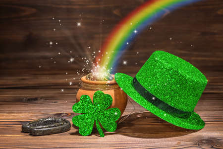 St Patricks day decoration with magic light rainbow pot full gold coins, horseshoe, green hat and shamrock on vintage wooden background, close up