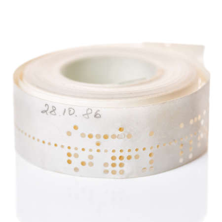 white perforated punched tape with old data  is isolated on background, close up