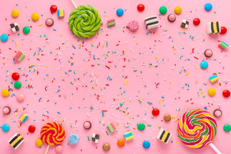 Foto de festive wreath background with assortment of colourful caramel candies, lollipops and sprinkles over pink - Imagen libre de derechos