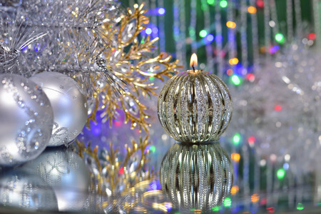 Christmas decorations with candle and silver balls on the mirror.