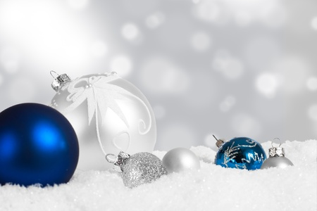 Silver and blue Christmas ornament display in snow