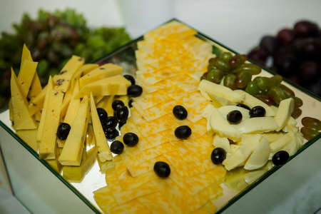 cheese assorted plateau with olives and grapes served on square mirror background in catering service