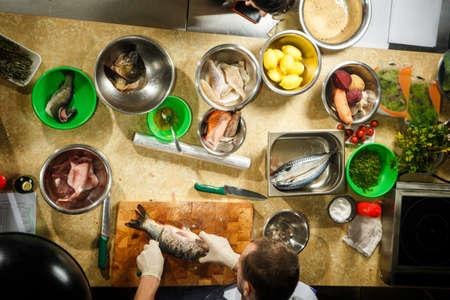 Foto de top view of fish fillets, lemons, carrot and beets, dill and salt lie in bowls on beige kitchen table - Imagen libre de derechos