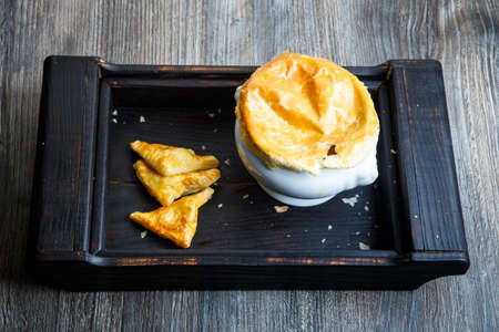 Foto de delicious white soup pot with bread on the top and three puff pastry cakes triangles served n black wooden tray - Imagen libre de derechos
