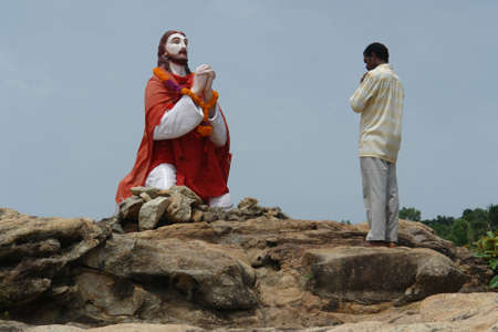 A man is praying to statue of Jesus