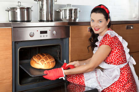 Young pretty housewife baking bread in kitchen oven