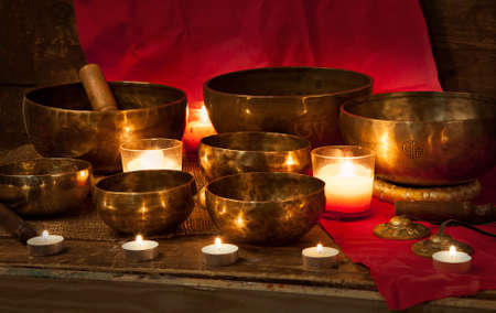Tibetan singing bowls with burning candles on a red background