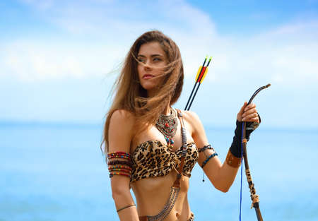 Photo for Portrait of a young beautiful girl in an Amazon costume with a bow and arrows on a background of sea and blue sky - Royalty Free Image