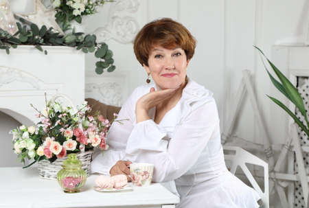 Foto für Portrait of an attractive middle aged woman sitting at a table with flowers in the living room bathed in light - Lizenzfreies Bild