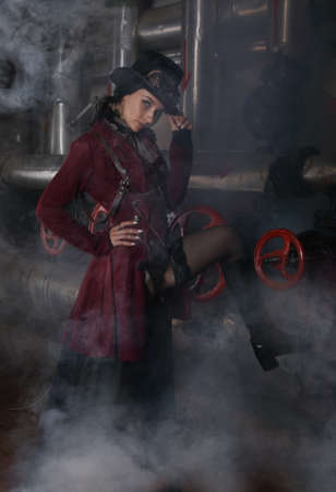 Foto de Pretty young steampunk woman shrouded in steam over industrial background with pipes and valves  - Imagen libre de derechos