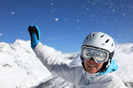 Photo for Portrait of a young woman in a ski suit and helmet on the background of  snow covered mountains  - Royalty Free Image