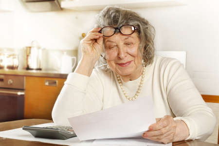 Photo pour An old lady sitting at a table in the kitchen looking through receipts with a calculator - image libre de droit