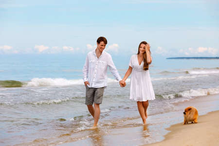 Photo pour Cute couple of young lovers with a Pomeranian dog walk along the beach on a sunny summer day - image libre de droit