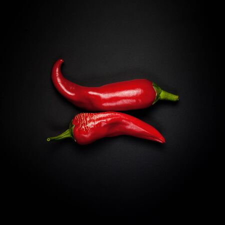 Two pods of red pepper on a black background
