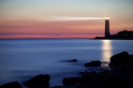 Photo pour Seascape at sunset. Lighthouse on the coast - image libre de droit