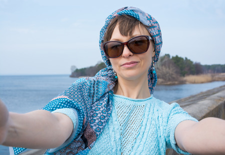 Beautiful woman taken picture of herself, selfie. Young woman photographed herself in front of the seascape.