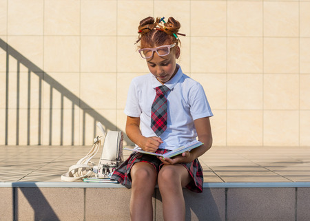 Photo pour A girl in school uniform with a funny hairdo with colored pencils in her hair and with books sits on the steps in front of the school and reads the book, prepares for the lesson - image libre de droit