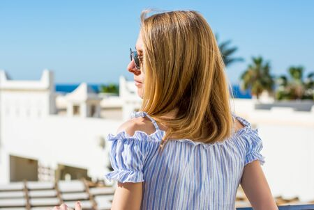Photo pour Young girl in sunglasses stands a back on the balcony and looks at the sea and palm trees. - image libre de droit