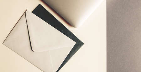 Envelopes and laptop on trendy ashen gray background. Mockup. Office minimalistic concept.