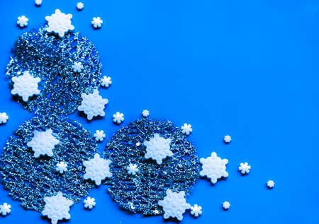Photo pour Silver decor, snowflake sprinkles and shiny star shaped glitters on blue background. Winter holidays concept. - image libre de droit